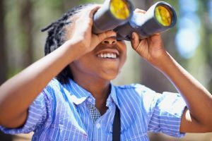Shot of a young boy out in the woods with a pair of binoculars